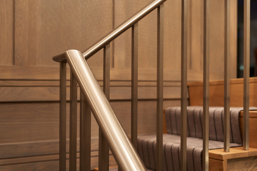 detail of wooden stairs with stainless handrail