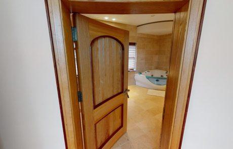 curved wooden door leading into bathroom