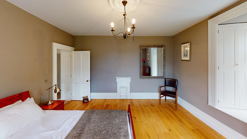 large bedroom with wooden floors